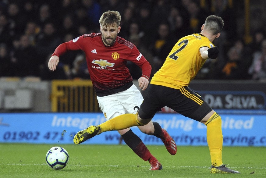 Wolverhampton's Matt Doherty vies for the ball with Manchester United's Luke Shaw, left, during the English Premier League soccer match between Wolverhampton Wanderers and Manchester United at the Molineux Stadium in Wolverhampton, England, Tuesday, April 2, 2019. (AP Photo/Rui Vieira)
