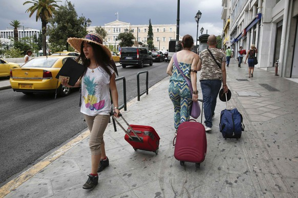 Tourists make their way around central Syntagma square in Athens July 24, 2014.  Greece is expecting record tourist arrivals this year, boosting an economy thirsting for revenues after four years of financial crisis and bringing back traditional tourists who had stayed away, according to the country's main tourism organization.