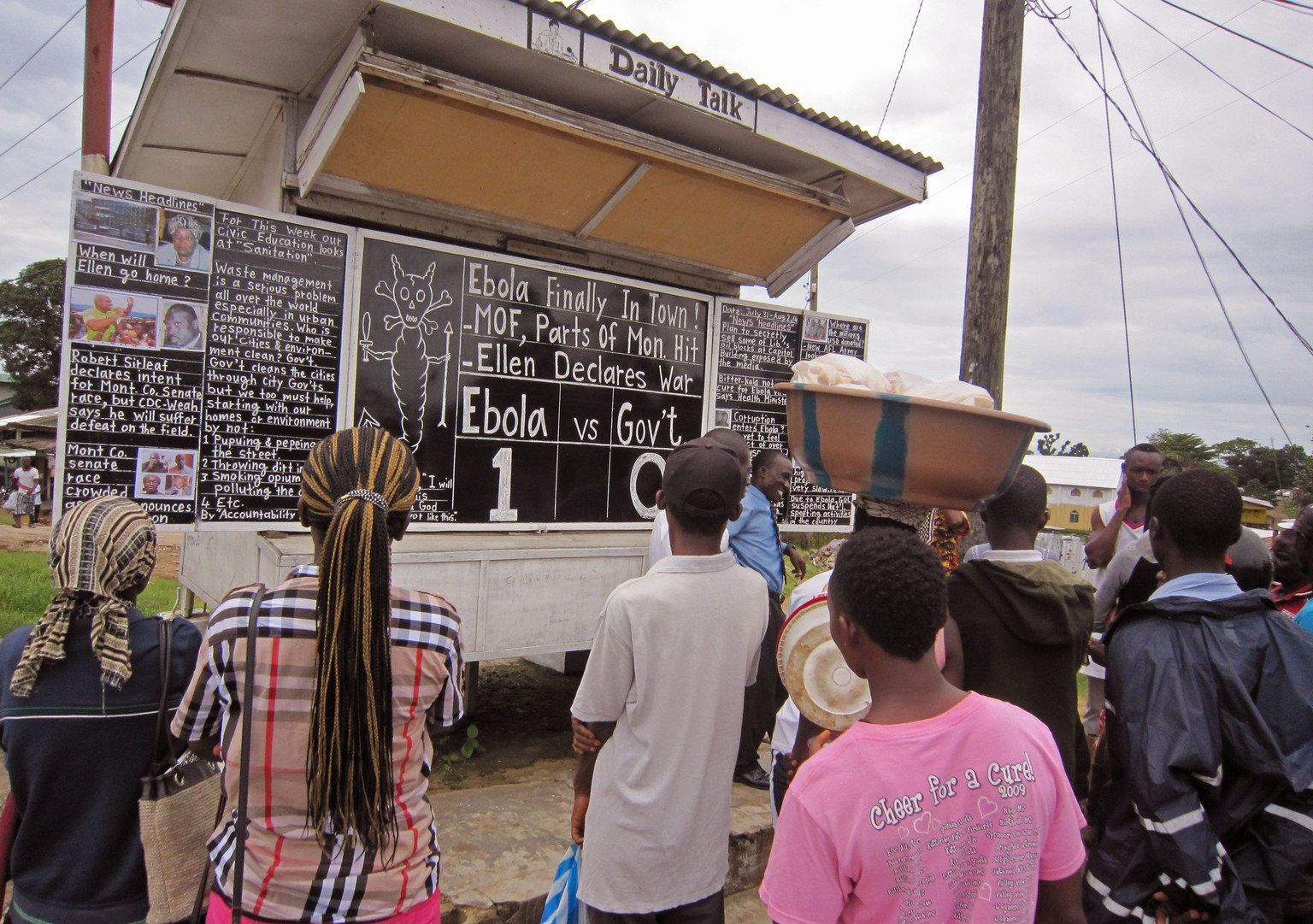Social Commentator Alfred Sirleaf, center rear,  gives comment on current events in Liberia including the deadly Ebola virus by speaking and writhing them down on a blackboard as people gather around to listen to him in Monrovia, Liberia, Thursday, July 31, 2014. The worst recorded Ebola outbreak in history surpassed 700 deaths in West Africa as the World Health Organization on Thursday announced dozens of new fatalities. (AP Photo/Jonathan Paye-Layleh)