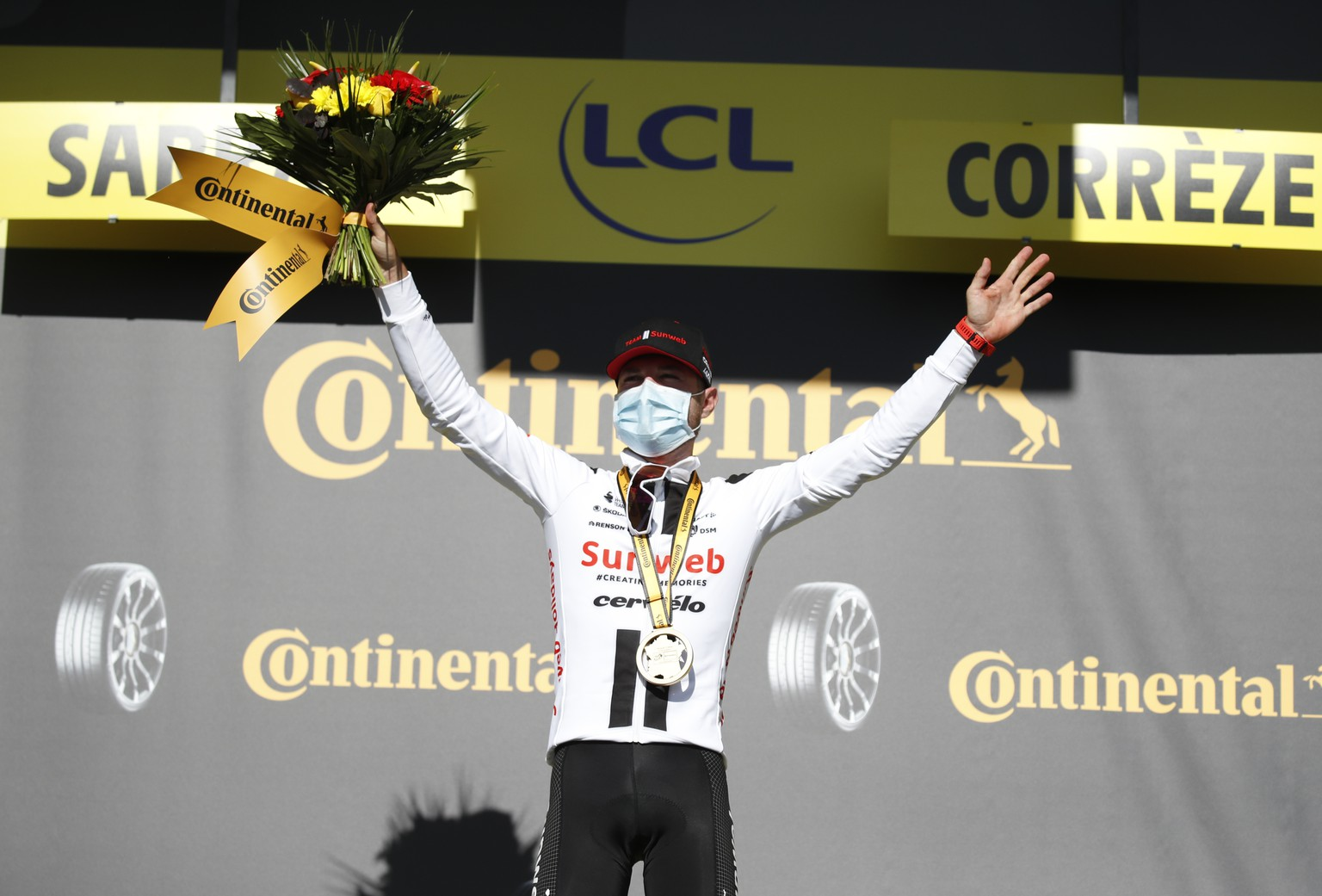 Switzerland's Marc Hirschi celebrates on the podium after winning the stage 12 of the Tour de France cycling race over 218 kilometers from Chauvigny to Sarran, Thursday, Sept. 10, 2020. (Sebastien Nogier/Pool via AP)