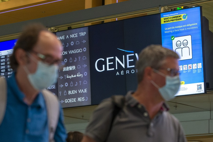 Passengers wearing face masks to protect of the COVID-19 passe in front of a information screen reading