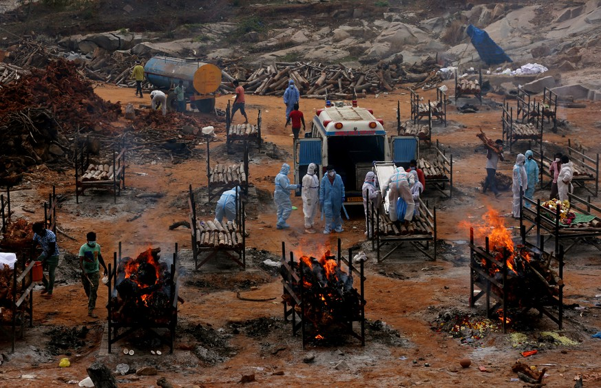epaselect epa09175681 Funeral pyres for COVID-19 victims burn during a mass funeral at a makeshift cremation ground at Giddenahalli in the outskirts of Bangalore, India, 03 May 2021. India recorded a massive surge of 368,147 fresh Covid-19 cases and 3,455 deaths in the last 24 hours.  EPA/JAGADEESH NV