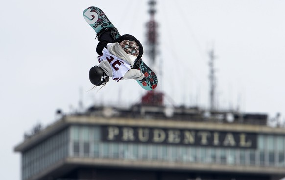epa05155406 An athlete performs a trick while making a jump at the Big Air Snowboarding competition held at Fenway Park, with the Prudential Tower seen in the background in Boston, Massachusetts, USA 11 February 2016. The Fenway Big Air competition takes place 11 and 12 February 2016, the first time snowboarding and skiing ever held at Fenway Park.  EPA/CJ GUNTHER