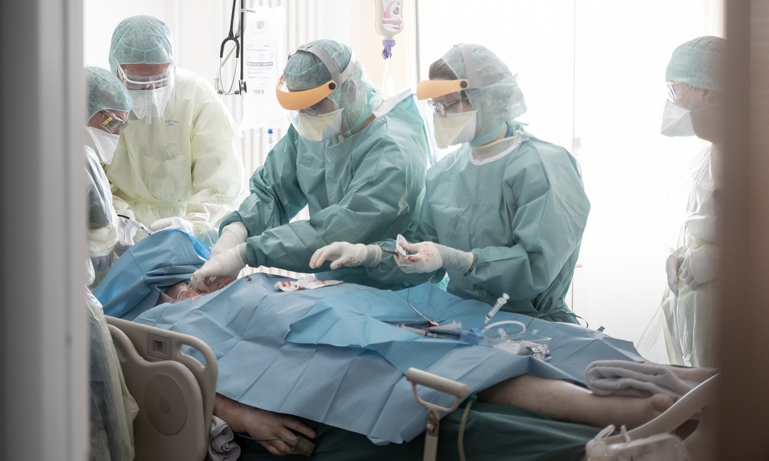 Doctors are executing a tracheotomy to a patient in Intensive Care in the pediatrics department at the regional hospital La Carita in Locarno, Switzerland, April 2, 2020. (KEYSTONE/Ti-Press/Pablo Gianinazzi)