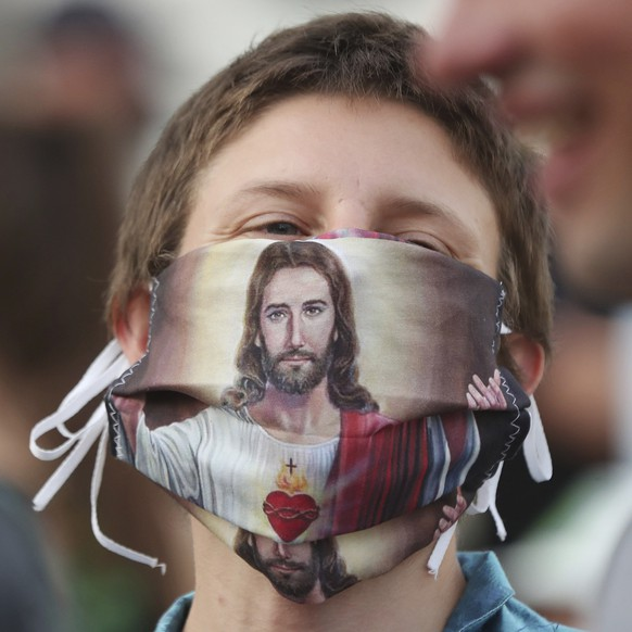 A participant wears a protective face mask with a picture of Jesus Christ on it as she takes part in a rainbow disco flashmob in front of the Presidential Palace in Warsaw, Poland, Thursday, June 11, 2020. Polish President Andrzej Duda signed a document called Family Card which is homophobic and discriminating in perception of LGBT community. (AP Photo/Czarek Sokolowski)