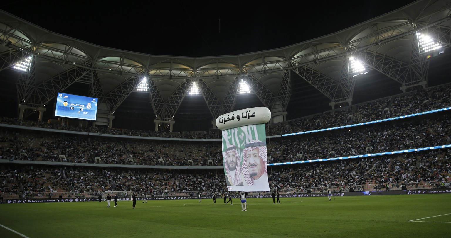 A banner is displayed on the pitch with pictures of Saudi King Salman, right, and Crown Prince Mohammed bin Salman, during halftime of the Spanish Super Cup semifinal soccer match between Real Madrid and Valencia at King Abdullah stadium in Jiddah, Saudi Arabia, Wednesday, Jan. 8, 2020. Words read in Arabic,
