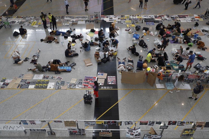 Protesters continue their sit-in rally at the airport in Hong Kong, Wednesday, Aug. 14, 2019. Flight operations resumed at the airport Wednesday morning after two days of disruptions marked by outbursts of violence highlighting the hardening positions of pro-democracy protesters and the authorities in the Chinese city that's a major international travel hub. (AP Photo/Vincent Thian)