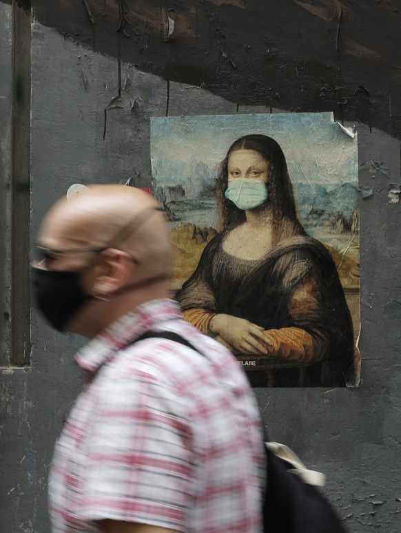 A man walks past a poster of Leonardo Da Vinci's Mona Lisa wearing a surgical mask and some obituaries, in Naples, Italy, Tuesday, Sept. 15, 2020. (AP Photo/Gregorio Borgia)