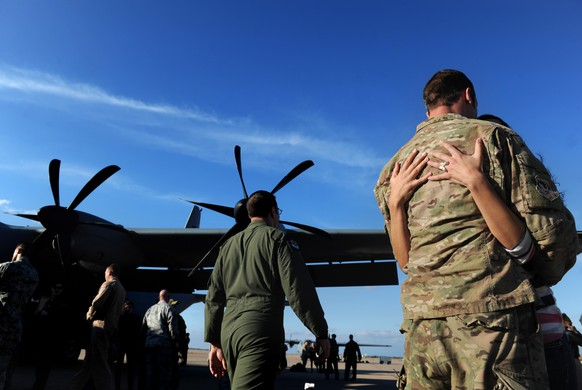 An airman is greeted at Dyess Air Force Base, Wednesday, Feb. 4, 2015, in Abilene, Texas. About 35 airmen flew supplies from Senegal to Liberia to aid in the fight against Ebola. (AP Photo/The Abilene Reporter-News, Nellie Doneva)