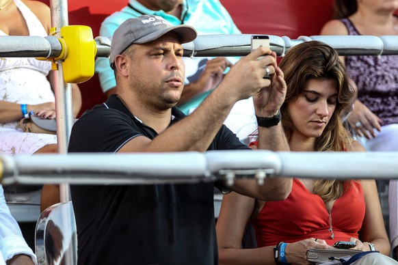 epa04098398 Former Brazilian player Ronaldo Luis Nazario de Lima (L) takes pictures during the ATP 500 final match between Spaniard Rafael Nadal and Ukranian Alexandr Dolgopolov at Rio de Janeiro Open in Brazil, 23 Febraury 2014. Woman on right is not identified.  EPA/Antonio Lacerda
