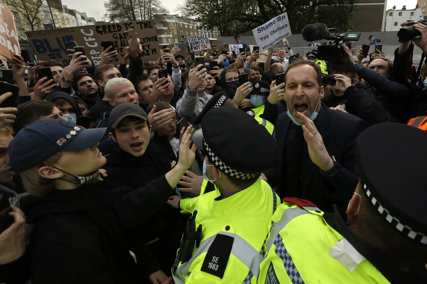 Chelsea former star goalkeeper Petr Cech, at right, behind a line of policemen, tries to calm down fans protesting outside Stamford Bridge stadium in London, against Chelsea's decision to be included amongst the clubs attempting to form a new European Super League, Tuesday, April 20, 2021. Reaction to the proposals from 12 clubs to rip up European soccer by forming a breakaway Super League has ranged from anger and condemnation to humor and sarcasm. (AP Photo/Matt Dunham)