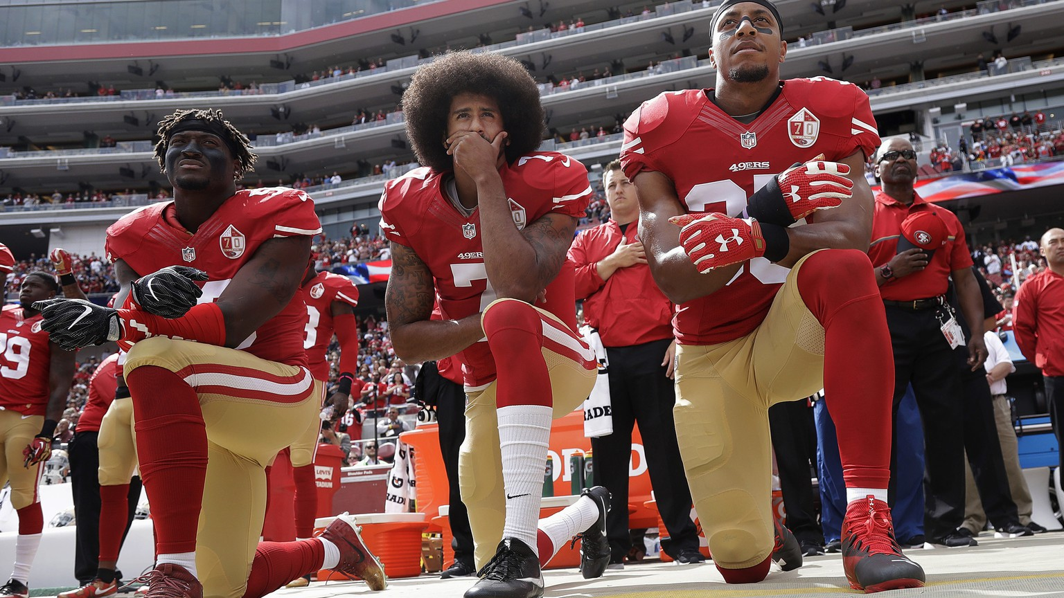 FILE - In this Oct. 2, 2016, file photo, San Francisco 49ers outside linebacker Eli Harold, left, quarterback Colin Kaepernick, center, and safety Eric Reid kneel during the national anthem before the team's NFL football game against the Dallas Cowboys in Santa Clara, Calif. Kaepernick accepted Sports Illustrated's Muhammad Ali Legacy Award from Beyonce on Tuesday night, Dec. 5, 2017, and promised that