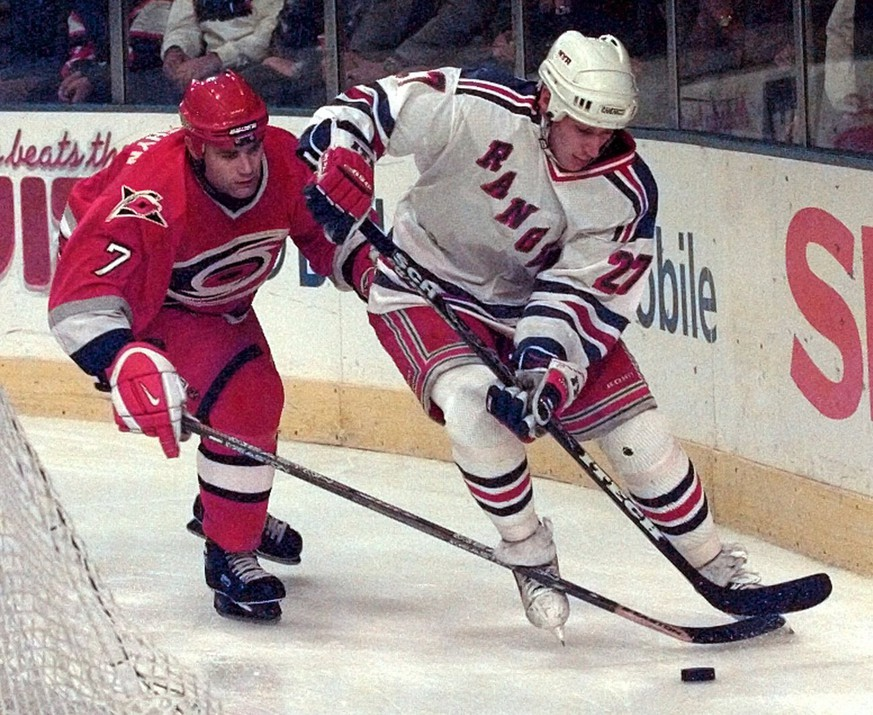 New York Rangers right winger Alexei Kovalev (27) tries to keep control of the puck in front of Carolina Hurricanes' Curtis Leschyshyn (7) as they skate behind the net during second period action Monday, Oct. 20, 1997, at Madison Square Garden in New York. The Rangers won 4-2. (AP Photo/Ron Frehm)