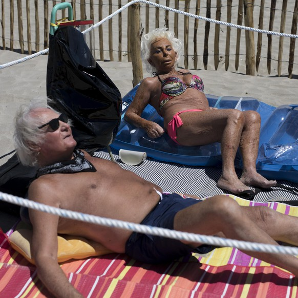 Mario and Monique sunbathe in an area marked to enforce social distancing measures in La Grande Motte, southern France, Sunday, May 24, 2020. Grateful French families flocked to the beach at La Grande Motte on the Mediterranean shore Sunday, swimming and sunbathing in areas carefully marked to keep them a safe distance from others. (AP Photo/Daniel Cole)