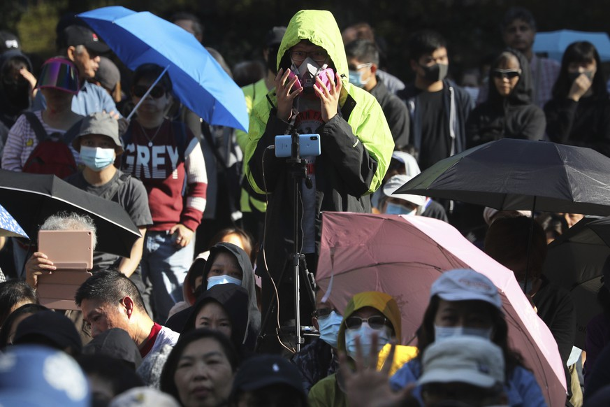 A protester wears a gas mask during a rally for students and elderly pro-democracy demonstrators in Hong Kong, Saturday, Nov. 30, 2019. Hundreds of Hong Kong pro-democracy activists rallied Friday outside the British Consulate, urging the city's former colonial ruler to emulate the U.S. and take concrete actions to support their cause, as police ended a blockade of a university campus after 12 days. (AP Photo/Ng Han Guan)