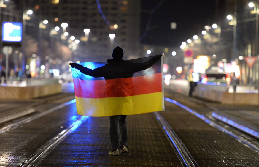 epaselect epa04634410 A participant in a rally of anti-Islamic Pegida (Patriotic Europeans against the Islamization of the West) movement stands on a street with a German flag in Dresden, Germany, 23 February 2015. Pegida has called for a new rally in Dresden for the first time since the split in the movement.  EPA/ARNO BURGI