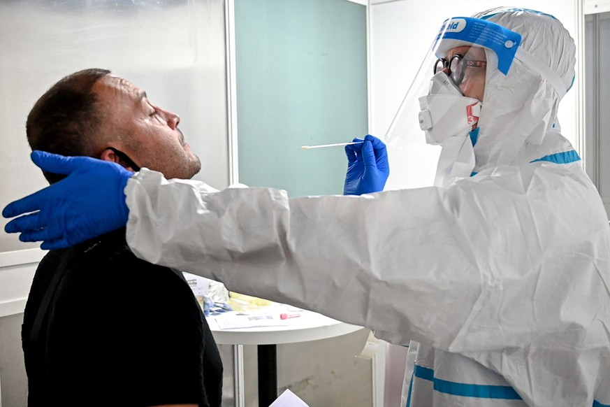 epa08568621 A traveler gets his swab sample collected in a walk-in test center for coronavirus at the International Airport in Duesseldorf, Germany, 27 July 2020. Within a few days, a test centre has now also been set up at Duesseldorf International Airport, where returnees from risk areas can be tested for COVID-19.  EPA/SASCHA STEINBACH