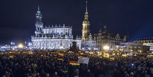 Participants of a rally called 'Patriotic Europeans against the Islamization of the West' (PEGIDA) wave with flags during a demonstration entitled 'Christmas With Pegida' in front of the Dresden Cathedral, or the Cathedral of the Holy Trinity, center, left, in Dresden, eastern Germany, Monday, Dec. 22, 2014. For the past ten weeks, activists protesting Germany's immigration policy and the spread of Islam in the West have been marching each Monday. (AP Photo/Jens Meyer)