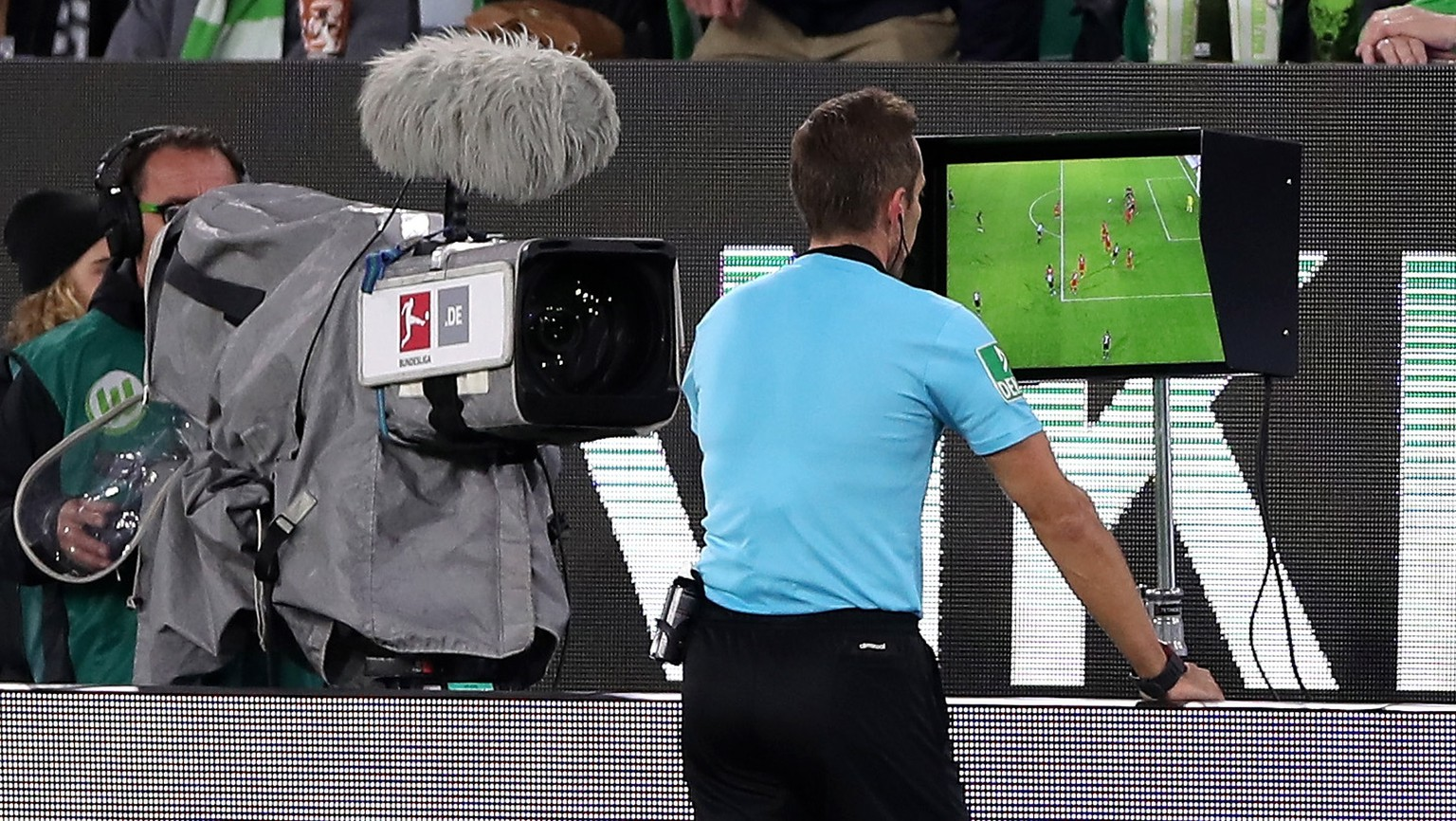 epa07954113 Referee Tobias Stieler (C) checks the VAR video review during the German Bundesliga soccer match between VfL Wolfsburg and FC Augsburg in Wolfsburg, Germany, 27 October 2019.  EPA/FRIEDEMANN VOGEL CONDITIONS - ATTENTION:  The DFL regulations prohibit any use of photographs as image sequences and/or quasi-video.
