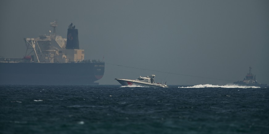 An Emirati coast guard vessel passes an oil tanker off the coast of Fujairah, United Arab Emirates, Monday, May 13, 2019. Saudi Arabia said Monday two of its oil tankers were sabotaged off the coast of the United Arab Emirates near Fujairah in attacks that caused