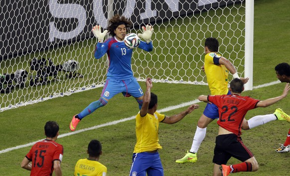 Mexico's goalkeeper Guillermo Ochoa, left,  saves a header by Brazil's Thiago Silva  during the group A World Cup soccer match between Brazil and Mexico at the Arena Castelao in Fortaleza, Brazil, Tuesday, June 17, 2014.  (AP Photo/Themba Hadebe)