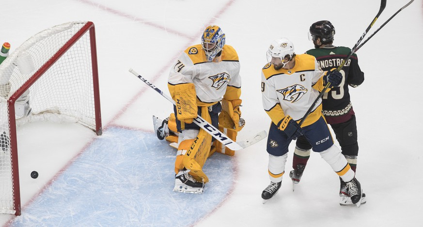 Nashville Predators goalie Juuse Saros (74) is scored on as Arizona Coyotes' Brad Richardson (15) and Predators' Filip Forsberg (9) battle in front of the net during first period NHL hockey action in Edmonton, Alberta, Friday, Aug. 7, 2020. (Jason Franson/The Canadian Press via AP)