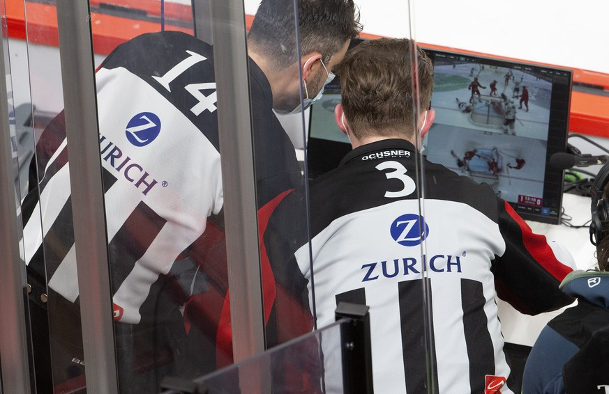 Head referee Mark Lemelin, and Head referee Manuel Nikolic, right, consults the video to check whether to award the goal, during a National League regular season game of the Swiss Championship between Lausanne HC and HC Lugano, at the Vaudoise Arena in Lausanne, Switzerland, Wednesday, February 17, 2021. The game is played behind closed doors due to the coronavirus COVID-19 pandemic. (KEYSTONE/Salvatore Di Nolfi)