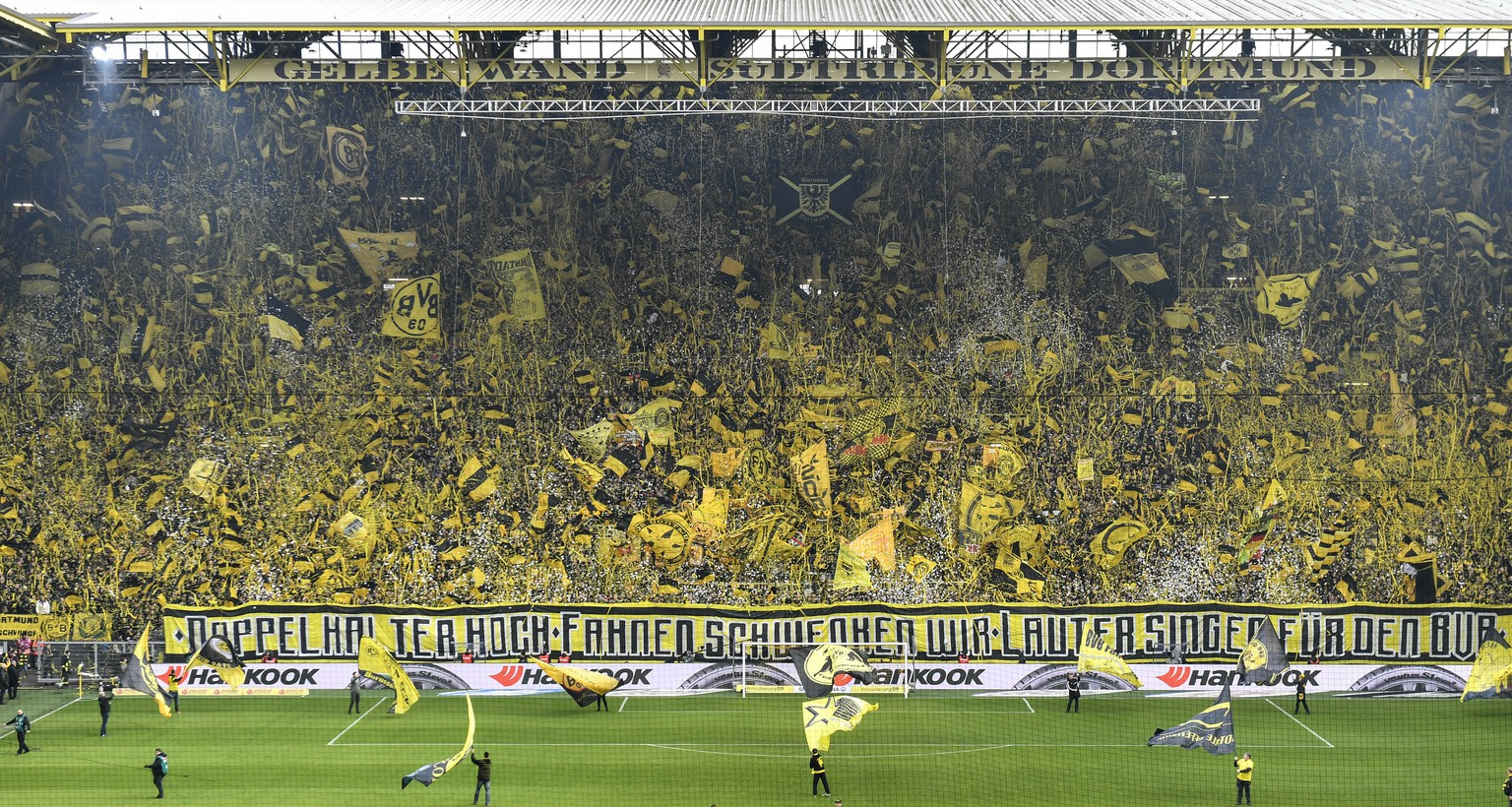 FILE - In this April 13, 2019 file photo, Borussia Dortmund's fans celebrate on the famous south tribune 'Gelbe Wand', the largest terrace for 24,454 standing spectators in European football, in the Signal Iduna Park stadium in Dortmund, Germany. Just days after narrowly losing out in the Bundesliga to Bayern Munich, Dortmund signed three internationals to better challenge the Bavarian powerhouse next season. Germany's Julian Brandt and Nico Schulz have joined from Bayer Leverkusen and Hoffenheim, respectively, while Belgium forward Thorgan Hazard has switched from Borussia Moenchengladbach. (AP Photo/Martin Meissner)