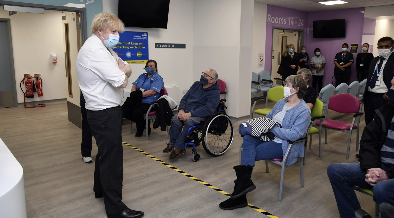 Britain's Prime Minister Boris Johnson meets people waiting for their vaccine during a visit to a coronavirus vaccination centre at the Health and Well-being Centre in Orpington, south-east London, Monday, Feb. 15, 2021. (Jeremy Selwyn/Pool Photo via AP)