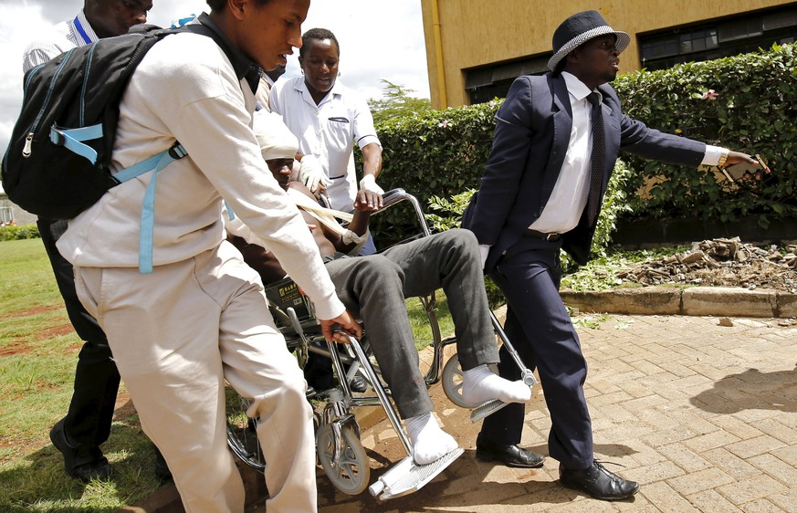 Students assist their colleague who was injured when he jumped from the lecture room during a security exercise at the Strathmore University in Kenya's capital Nairobi, November 30, 2015.  Police conducted a security exercise at a campus in Kenya's capital Nairobi on Monday that sparked panic over a feared attack and ended with several students injured. Students from Strathmore University were not informed about the security drill and panicked in fear the exercise was another al Shabaab attack. REUTERS/Thomas Mukoya