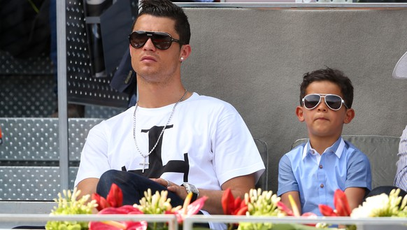 MADRID, SPAIN - MAY 08:  Real Madrid footballer Cristiano Ronaldo and his son Cristiano Ronaldo Junior watch Rafael Nadal of Spain against Jarkko Nieminen of Finland in their third round match during day six of the Mutua Madrid Open tennis tournament at the Caja Magica on May 8, 2014 in Madrid, Spain.  (Photo by Clive Brunskill/Getty Images)