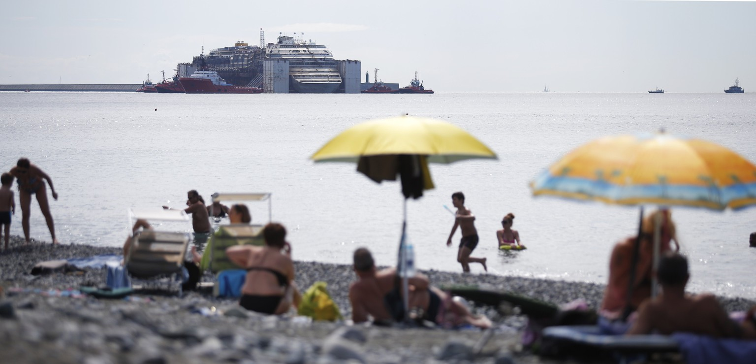 People take in the sun on the beach as the refloated wreck of the Costa Concordia cruise liner is towed to the Italian port of Genova on July 27, 2014. The wreck of the Costa Concordia entered the Italian port of Genoa on July 27, ending the cruise liner's final journey to be scrapped two and a half years after it capsized at a cost of 32 lives. The once-luxury liner was dragged into Genoa's Voltri port by several tug boats, four days after leaving its wreck site off the Tuscan island of Giglio in an unprecedented salvage operation. AFP PHOTO / MARCO BERTORELLO