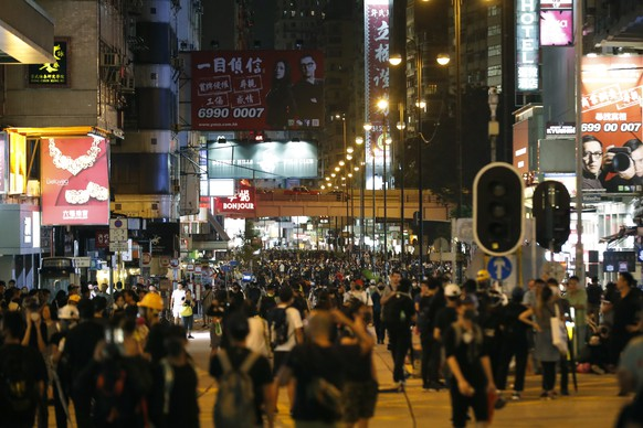 Protestors gather along a street in the Mong Kok neighborhood during a demonstration in Hong Kong, Saturday, Aug. 3, 2019. Hong Kong protesters removed a Chinese national flag from its pole and flung it into the city's iconic Victoria Harbour on Saturday after a pro-democracy rally once again continued into the evening despite police warnings to stick to a short, pre-approved route. (AP Photo/Vincent Thian)