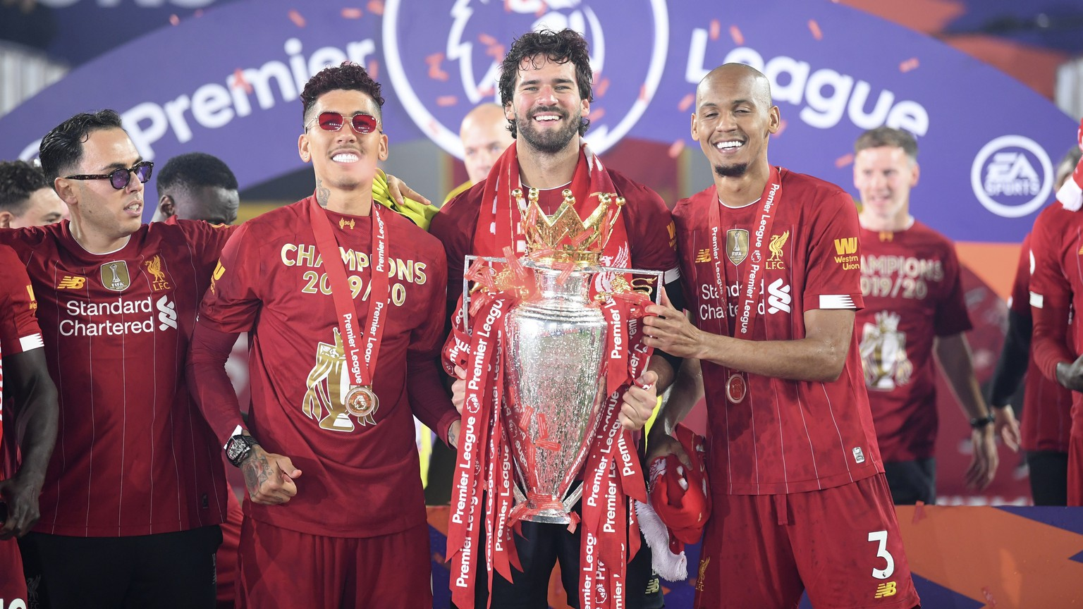 Liverpool's Fabinho, right, Liverpool's goalkeeper Alisson, center, and Roberto Firmino, all from Brazil, celebrate with the English Premier League trophy following the English Premier League soccer match between Liverpool and Chelsea at Anfield Stadium in Liverpool, England, Wednesday, July 22, 2020. Liverpool are champions of the EPL for the season 2019-2020. The trophy is presented at the teams last home game of the season. Liverpool won the match against Chelsea 5-3. (Laurence Griffiths, Pool via AP)