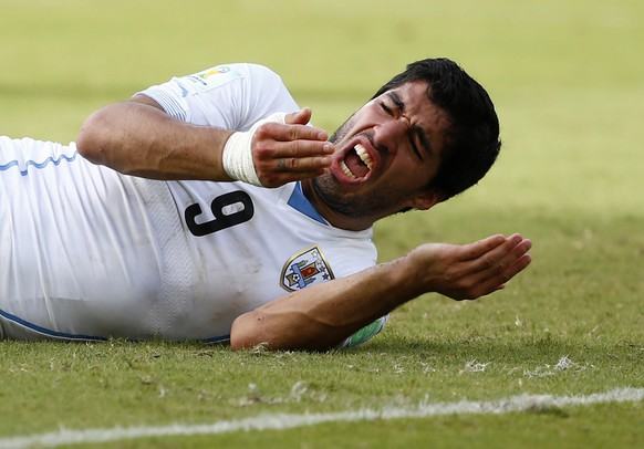 Uruguay's Luis Suarez reacts after clashing with Italy's Giorgio Chiellini during their 2014 World Cup Group D soccer match at the Dunas arena in Natal in this June 24, 2014 file photograph. Uruguay striker Suarez was banned for nine matches by FIFA on June 26, 2014 after being found guilty of biting Italian defender Chiellini on June 24, 2014. Suarez was also banned from any football-related activity for four months and fined 100,000 Swiss francs ($111,000). REUTERS/Tony Gentile/Files (BRAZIL  - Tags: SOCCER SPORT WORLD CUP)