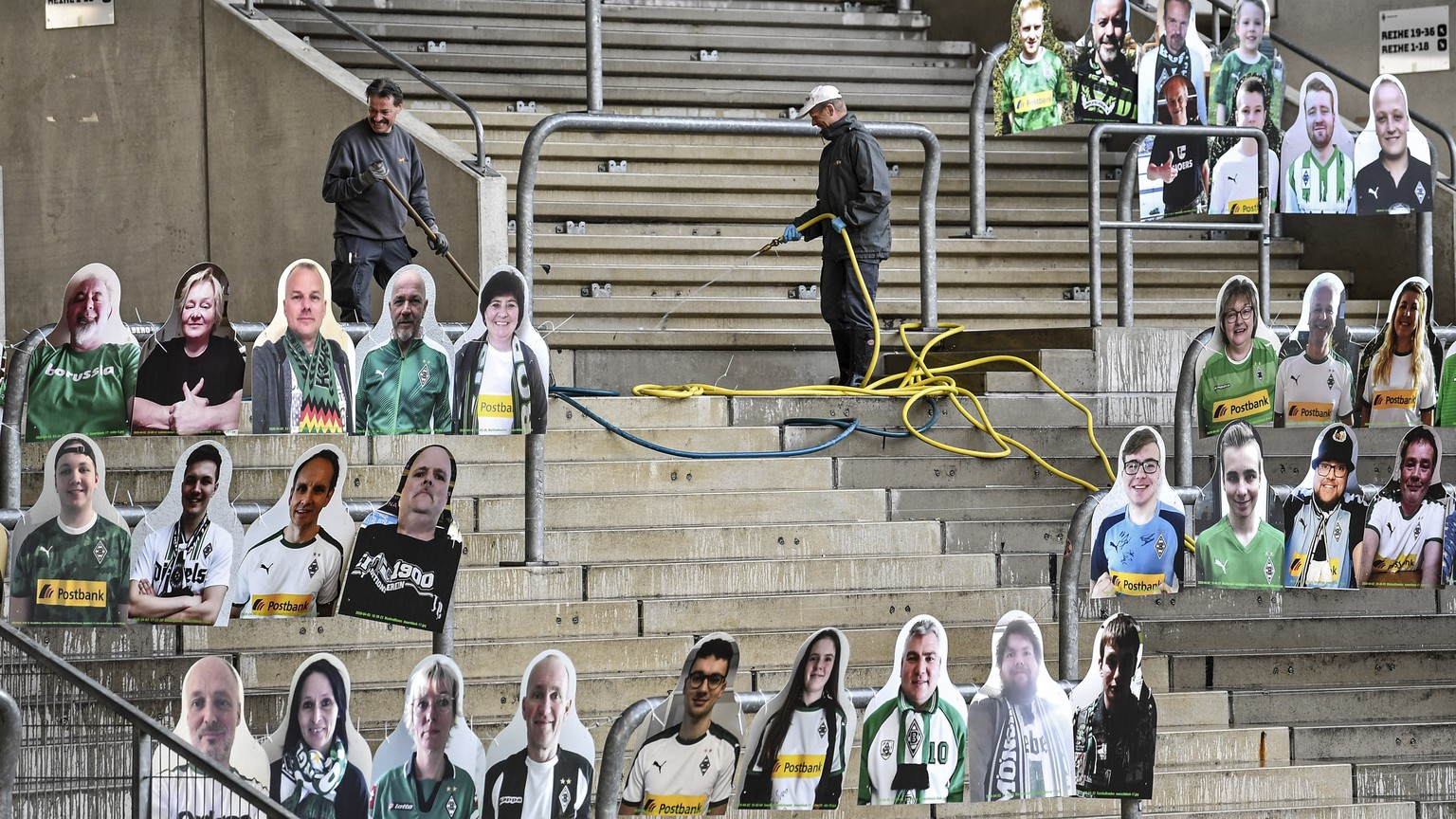 Workers clean the supporters tribune where portraits of fans of German Bundesliga soccer club Borussia Moenchengladbach are set in the stadium in Moenchengladbach, Germany, Thursday, April 16, 2020. All major events in Germany are suspended due to the coronavirus outbreak until the end of August, the German Bundesliga suspended all matches until April 30, 2020. (AP Photo/Martin Meissner)