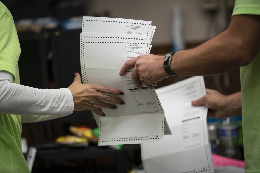 Poll workers sort out early and absentee ballots at the Kenosha Municipal building on Election Day, late Tuesday, Nov. 3, 2020, in Kenosha, Wis. (AP Photo/Wong Maye-E)