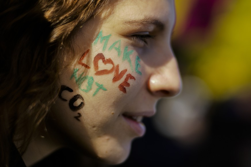 A student painted her face with a slogan attends a protest of the Fridays for Future movement in Berlin, Friday, Oct. 18, 2019. (AP Photo/Markus Schreiber)