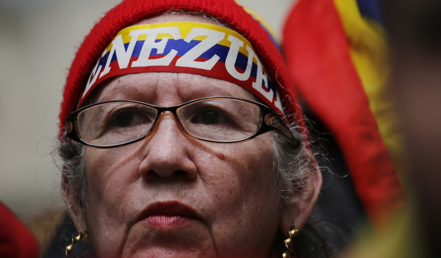 A woman waits for the arrival of Juan Guaido at a public plaza where he is expected to speak in Caracas, Venezuela, Friday, Jan. 25, 2019. Guaido is an opposition leader who declared himself interim president on Wednesday. (AP Photo/Fernando Llano)