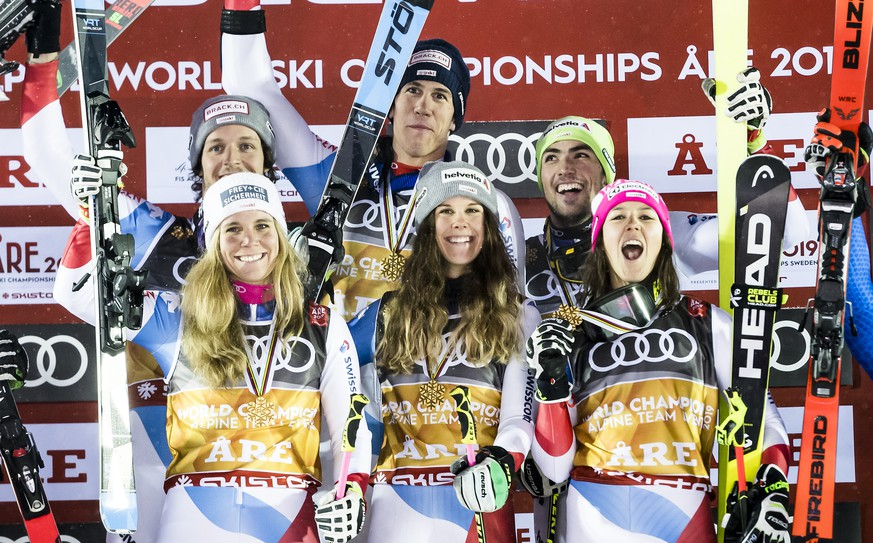 Team of Austria, left, team of Switzerland with Sandro Simonet, Ramon Zenhaeusern, Andrea Ellenberger, Aline Danioth, Wendy Holdener and Daniel Yule, center, team of Italy, right, celebrate during the medals ceremony after the Alpine Team Event at the 2019 FIS Alpine Skiing World Championships in Are, Sweden Tuesday, February 12, 2019. (KEYSTONE/Jean-Christophe Bott)