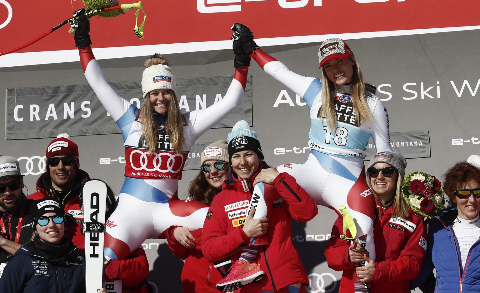 Switzerland's Lara Gut-Behrami, winner of an alpine ski, women's World Cup downhill, top right, celebrates with second-placed Switzerland's Corinne Suter, and the Swiss team, in Crans Montana, Switzerland, Friday, Feb. 21, 2020. (AP Photo/Gabriele Facciotti)