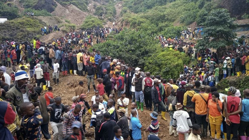 People gather at the scene of a gold mine collapse near the town of Kamituga, South Kivu province, in eastern Congo Friday, Sept. 11, 2020. More than 50 people are dead after landslides collapsed three artisanal gold mines near the town of Kamituga in eastern Congo's South Kivu province on Friday, officials said. (Jeff Mwenyemali/Maisha RDC via AP)