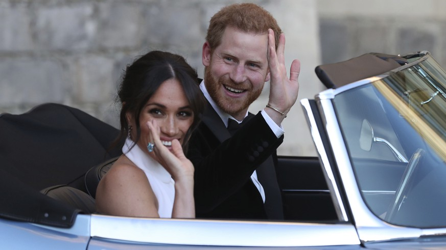 FILE - In this Saturday, May 19, 2018 file photo the newly married Duke and Duchess of Sussex, Meghan Markle and Prince Harry, leave Windsor Castle in a convertible car after their wedding in Windsor, England, to attend an evening reception at Frogmore House, hosted by the Prince of Wales. Prince Harry and his wife Meghan are ending their lives as senior members of Britain's royal family and starting an uncertain new chapter as international celebrities and charity patrons. In January the couple shocked Britain by announcing that they would step down from official duties, give up public funding, seek financial independence and swap the U.K. for North America. The split becomes official on March 31. (Steve Parsons/pool photo via AP, File)
