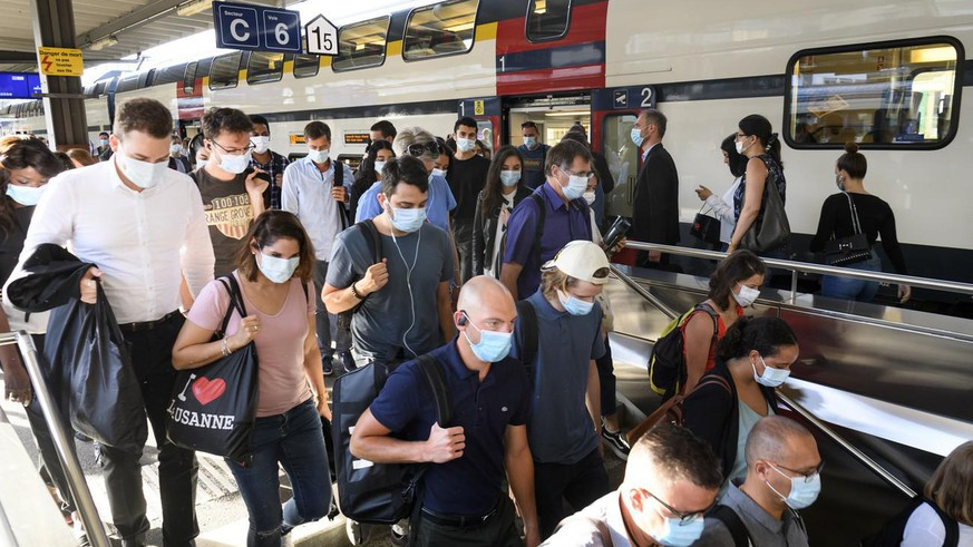 People wearing protective mask get out a SBB CFF train during the coronavirus disease (COVID-19) outbreak, at the train station CFF in Lausanne, Switzerland, Monday, July 6, 2020. In Switzerland, from Monday 6 July, people aged 12 and over must wear a mask in all public transport, trains, trams and buses, as well as in cable cars and boats. (KEYSTONE/Laurent Gillieron)