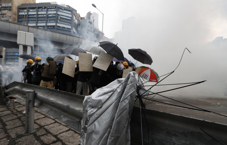 Protesters react to tear gas during a face off with riot police at Yuen Long district in Hong Kong Saturday, July 27, 2019. Police in Hong Kong shot tear gas at protesters who defied authorities' warnings not to march in a neighborhood where six days earlier a mob apparently targeting demonstrators brutally attacked people in a commuter rail station. (AP Photo/Bobby Yip)