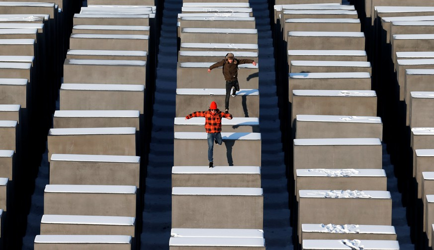FILE PHOTO: People jump from concrete elements of the Holocaust memorial in Berlin, Germany, January 25, 2013. REUTERS/Fabrizio Bensch/File Photo