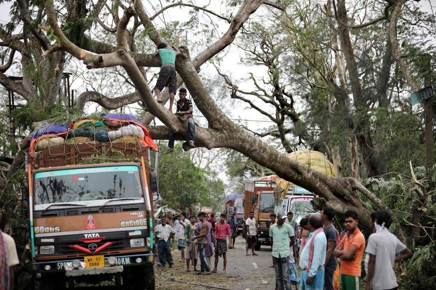 epa08435311 Commuters wait as locals try to remove an uprooted tree from the main road after Cyclone Amphan made landfall, in Bokkhali village near the Bay of Bengal, India, 21 May 2020. The Odisha government and Bengal government are considering a mass evacuation of the area.  EPA/PIYAL ADHIKARY