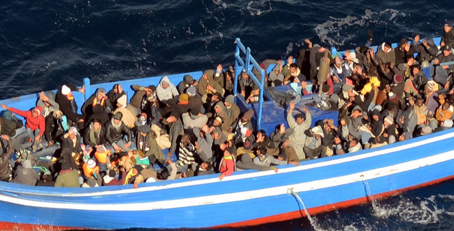 epa04036677 A handout photograph provided by the Italian Navy shows a boat with 200 migrants, off the coast of Lampedusa, Italy, 22 January 2014. The Italian navy said on 22 January it has sent a frigate and helicopter to rescue some 200 migrants onboard a boat in the central Mediterranean. The vessel was seen around 90 nautical miles (170 kilometres) south of the island of Lampedusa, Italy's southern outpost which is roughly halfway between Sicily and Tunisia.  EPA/ITALIAN NAVY / HANDOUT  HANDOUT EDITORIAL USE ONLY/NO SALES