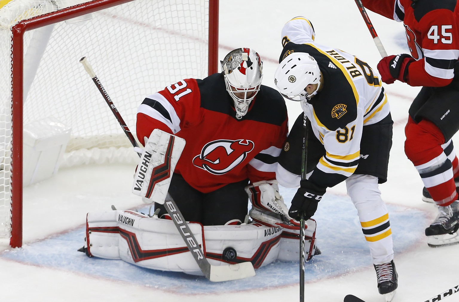 New Jersey Devils goaltender Gilles Senn (31) makes a save against Boston Bruins left wing Anton Blidh (81) during the third period of an NHL preseason hockey game, Monday, Sept. 16, 2019, in Newark, N.J. (AP Photo/Noah K. Murray)