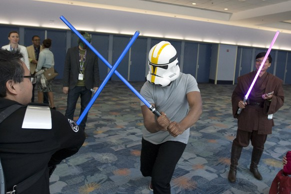Star Wars: The Force Awakens cast member John Boyega disguises his identity with a helmet and engages unknowing fans in a light saber fight scene at the Star Wars Celebration convention in Anaheim, California, April 16, 2015. The Star Wars Celebration runs through April 19 at the Anaheim Convention Center.  REUTERS/David McNew
